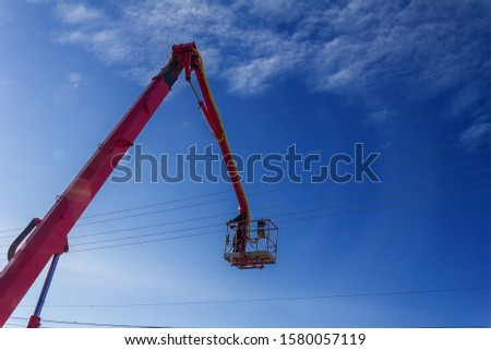 working electrician working at height on hydraulic aerial platform against the blue sky