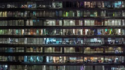 Working evening in glass business centre office building with numerous offices with glass walls and illuminated windows timelapse. People sitting at desks
