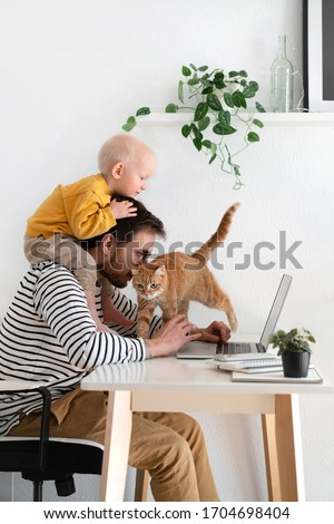 Working from home. Father freelancer with baby and cat in home office at his desk. Family indoors