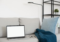Working from home, laptop computer with blank empty white screen display monitor on sofa. Mock up, copy space. Entrepreneur, finance, new business, home office, e-learning, journalist concept