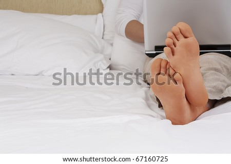 Working from home. Man relaxing in bed using laptop, close up on male foots.