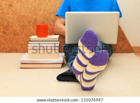 Working from home. Man relaxing in bed using laptop, close up on male foots in socks.