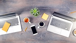 Working from home setup. Two laptopsand tea coffee mugs on wooden rustic desk. remote working or studying. Working space at home or distance learning banner or isolation lifestyle. top view