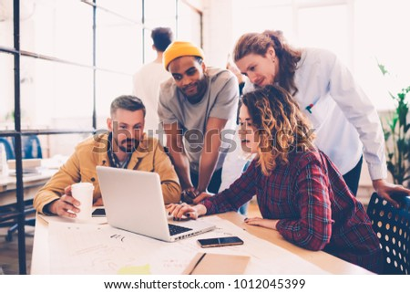 Working group discussing ideas for project sharing opinions while checking business plan on laptop, killed female web designer presenting to colleagues her job using netbook in coworking space