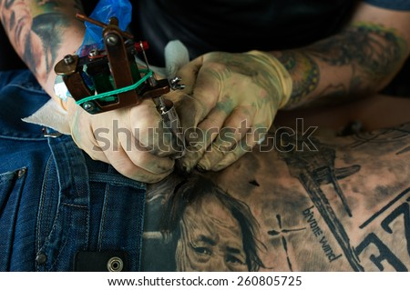 Working hands of tattoo master. Closeup