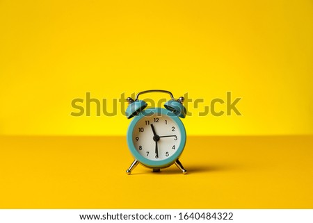 Working hours and overtime work. Hurry work, concept. Clock on yellow background.