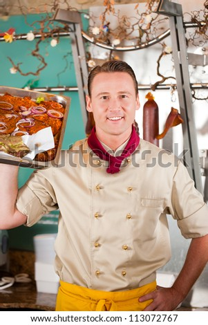 Working in a butchers shop - a butcher with barbeque steaks