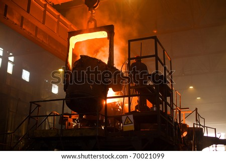 Working in a foundry. Red color is a reflection of the molten metal.