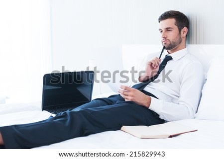Working in hotel room. Thoughtful young man in shirt and tie examining document while lying in bed at the hotel room