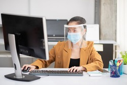 working in the business office look a computer while wearing a mask and face shield for the prevention and prevention of coronary or Covid-19 virus infection.