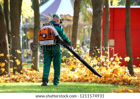 Working in the Park removes autumn leaves with a blower