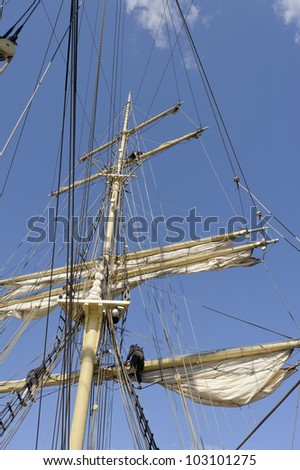 Working in the rigging of a brig