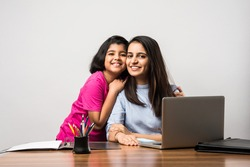 Working Indian mom works from home office with kidin pandemic. Woman and cute child using laptop. Freelancer workplace in cozy home. Happy mother and daughter.
