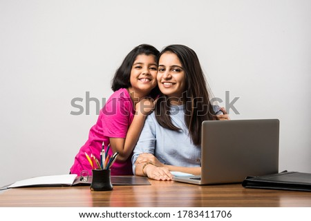 Working Indian mom works from home office with kid in pandemic. Woman and cute child using laptop. Freelancer workplace in cozy home. Happy mother and daughter.