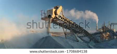 Photo of  Working industrial equipment of a crushing and processing plant in a plume of white stone dust, panorama.