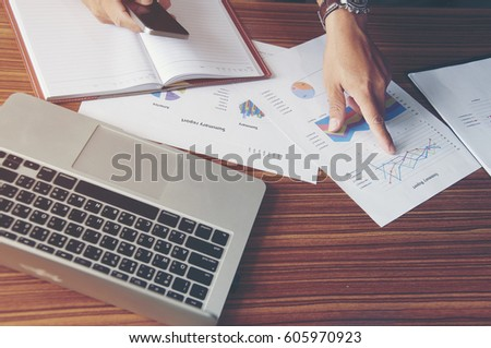 Working man viewing report (summary report,financial report,annual report),laptop on table