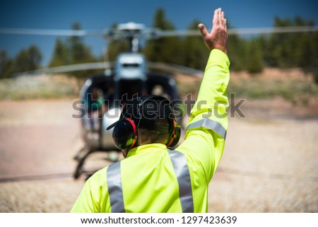 Working man wearing headset and yellow reflective jacket with his hand upwards toward the sky signals to blurred helicopter with tourists to start its journey above the Grand Canyon National Park #1297423639