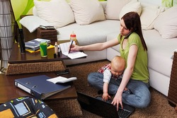 Working mom with baby in her chaotic home office