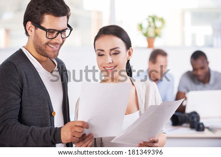 Working moments. Two cheerful business people holding documents and smiling while two people working on background