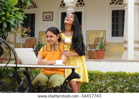 working Mother and daughter enjoying house garden