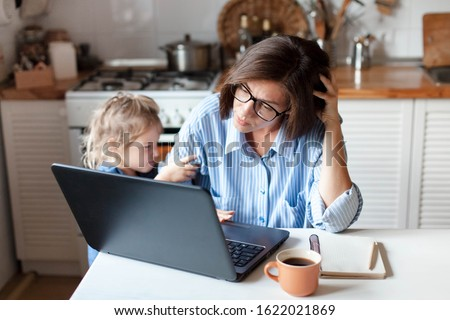 Working mother in home office. Unhappy woman and child using laptop. Sad and angry daughter needs attention from busy exhausted mom. Freelancer workplace in kitchen. Female business. Lifestyle moment.