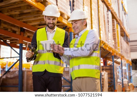 Working nuances. Professional warehouse manager holding a tablet while talking to his subordinate
