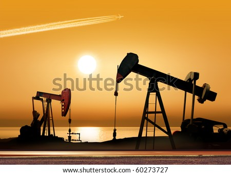 Working oil pump in rural place at sunset