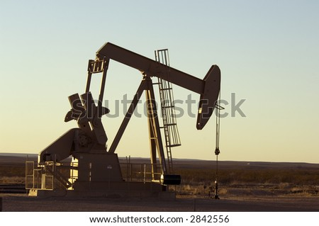 Working oil pump in rural Texas at sunset - stock photo