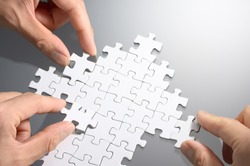 Working on an arrow shaped jigsaw puzzle. Concept image of making growth strategy.