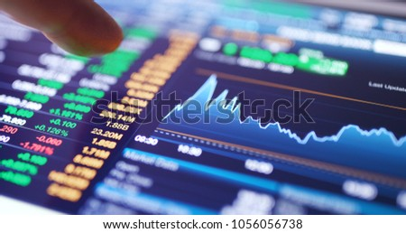 Working on digital tablet with stock market graph