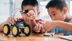 Working on Handmade car model, construction on electronic. Concentrated boy creating robot at lab. Early development, diy, innovation, modern technology concept.