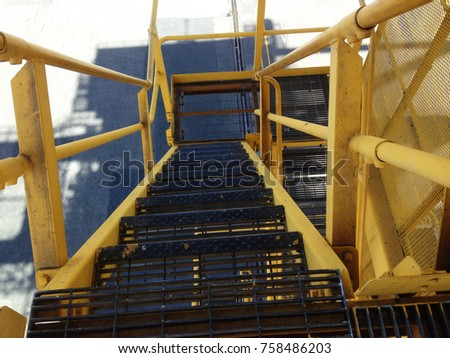 Working on High. Safety first for your work. Look out from the top step and step down the stairs carefully. Standing on black and yellow stairs.