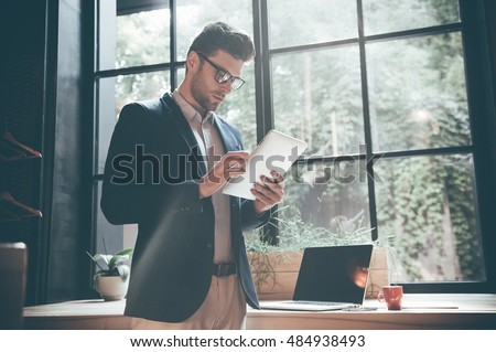 Working on new tablet. Low angle view of confident young man working on digital tablet while standing in front of the big window in office or cafe