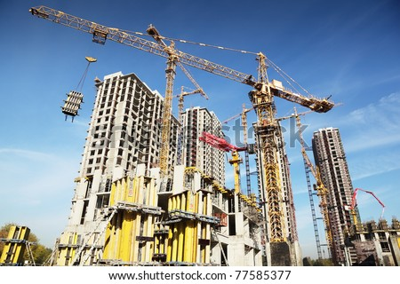 Working on place with many tall buildings under construction and cranes under a blue sky