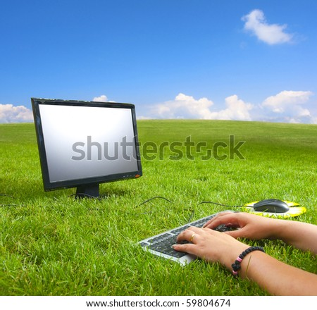 Working on the computer in the middle of the beautiful green meadow and under the blue sky on the sunny summer day.