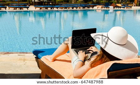 Working on travel, girl in a white hat with a laptop near the pool. Work on vacation, work on vacation. #647487988