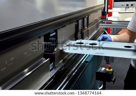 Working operator at a manufacturing plant bending sheet metal on a sheet bending machine.  Electric press brake