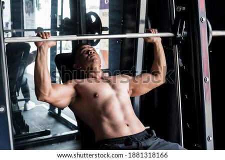 Working out and training scene - A shirtless asian 40 year old fit male does incline bench presses on a Smith Machine. Stock photo ©