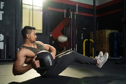 Working out at GYM concept. Young Asian handsome man working out his abdominal muscles by holding the medicine twist left and right sitting in the modern loft gym. Health and fitness concept.