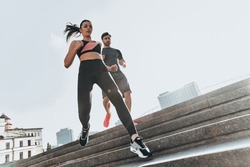 Working out on the stairs. Low angle view of young couple in sport clothing running down the stairs together