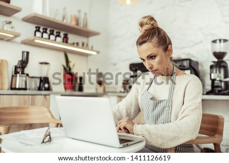 Working place. Focused smart cafe owner sitting at the table working at her laptop.