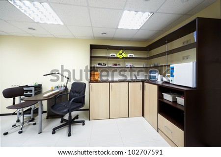 Working place of manicurist and shelves with towels, cosmetics