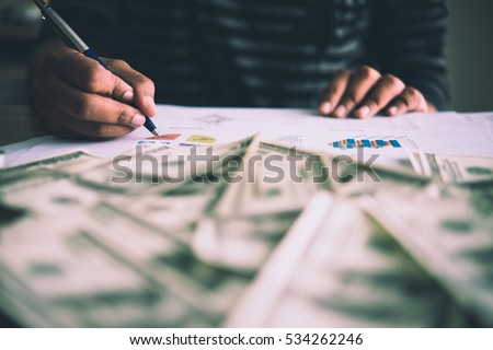 Working place of trader. The table covered by cash notes, financial charts. Business financial working.
