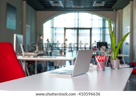 Working Place on grey Table with Laptop Computer green Flower red Chair and Pencils in modern Office interior with large Window on Background