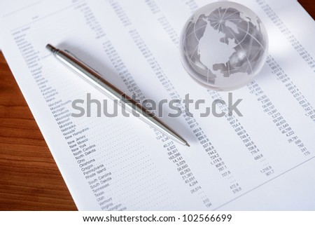 Working place with pen, glass globe and papers.