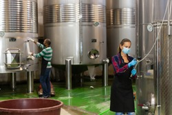 Working process at modern winery, woman worker in protective mask working with fermentation tank