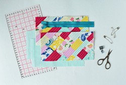 Working process: colorful quilt, fabric, zipper, embroidery scissors , quilting pins, sewing foot and acrylic ruler on white background