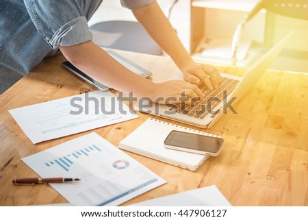 Working process modern office. Young finance manager working wood table with new business startup. Typing contemporary laptop. Horizontal. Film effect. Blurred background #447906127