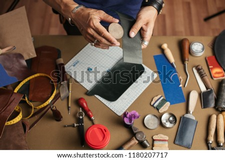 Working process of hand made leather wallet production in the leather workshop. Male hands close up holding crafting tool and working with leather. #1180207717