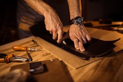 Working process of the leather belt in the leather workshop. Man holding crafting tool and working. Tanner in old tannery. Wooden table background.